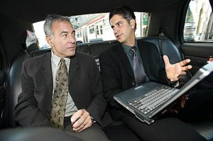 Two business men in car with laptop talking