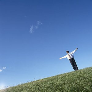 man standing on grass with hands outstretched