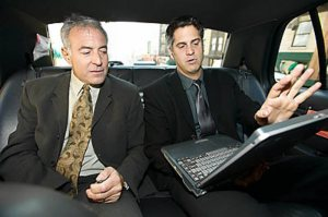 two men sitting in back of cab looking at a laptop computer