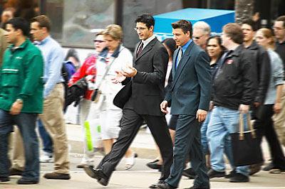 two men walking across street talking