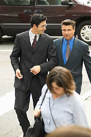 two business men crossing city street.