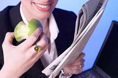 Businesswoman eating apple while reading newspaper uid 1179928