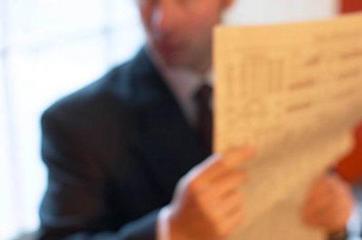 Blur of Caucasian businessman reading newspaper beside window uid 1172586