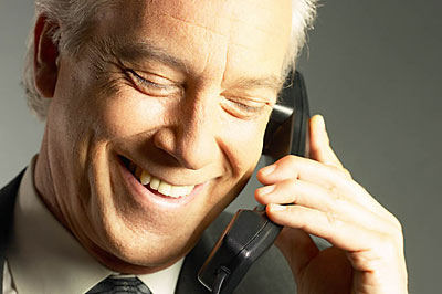 Laughing businessman talking on telephone uid 1280280