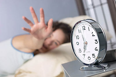 Woman reaching for alarm clock uid 1281547
